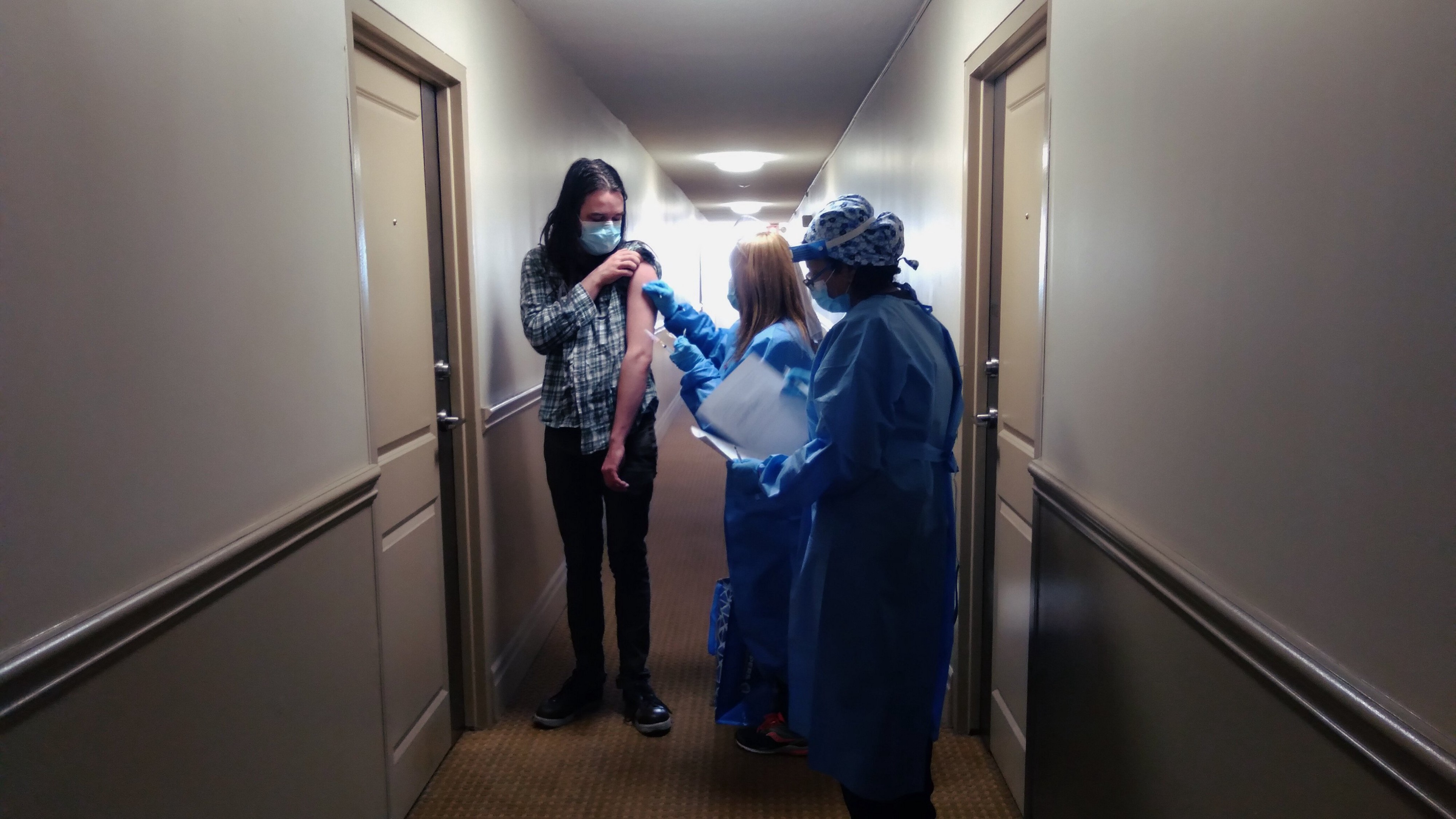 woman in hallway rolls up sleeve as two workers in PPE stand by