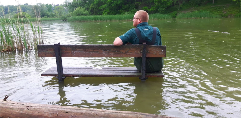 a man sits on a partially submerged bench