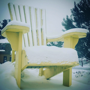 a giant yellow chair covered in snow