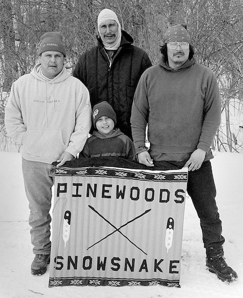 """Three men and a boy with a banner reading """"Pinewoods Snowsnake"""""""