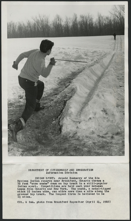 black and white photo of young holding a wooden dowel on a snow track