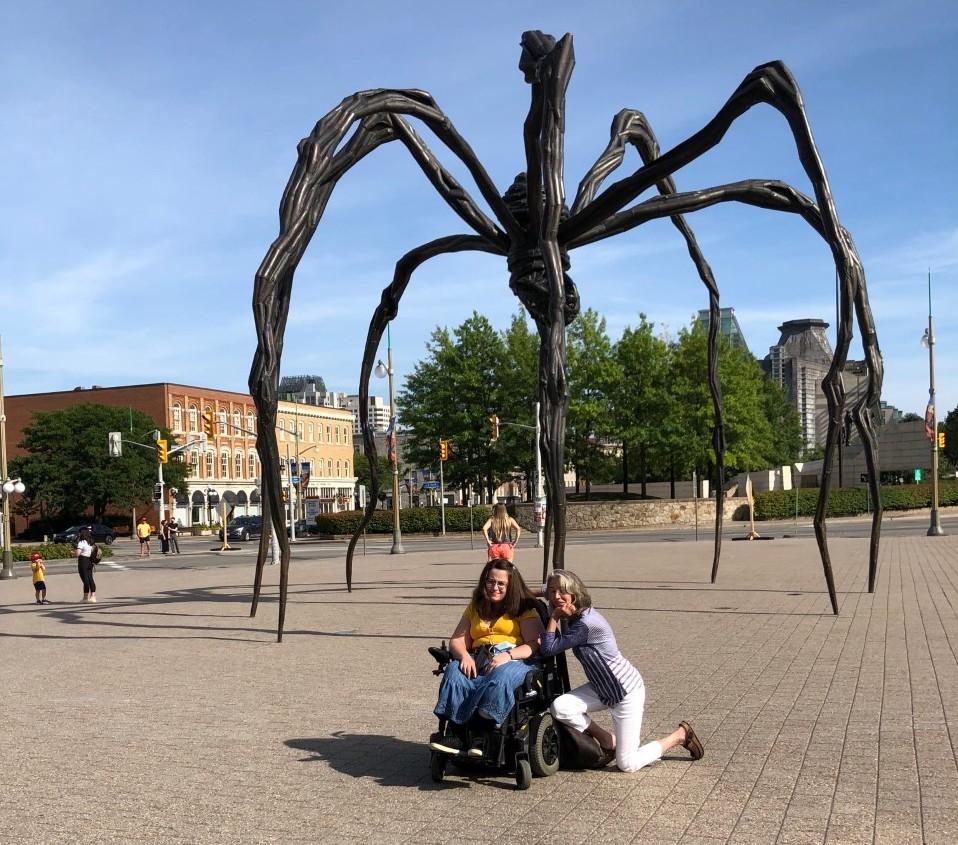 two women, one in wheelchair, under a large spider sculpture