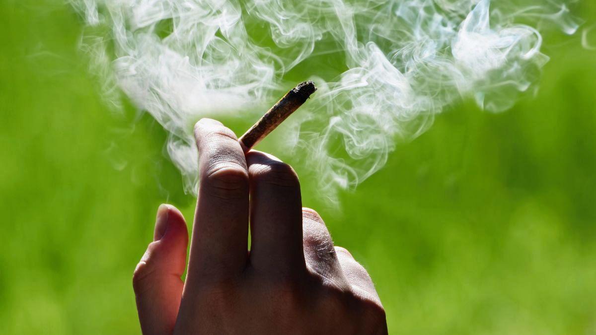 A man's hand holds a smoking marijuana cigarette