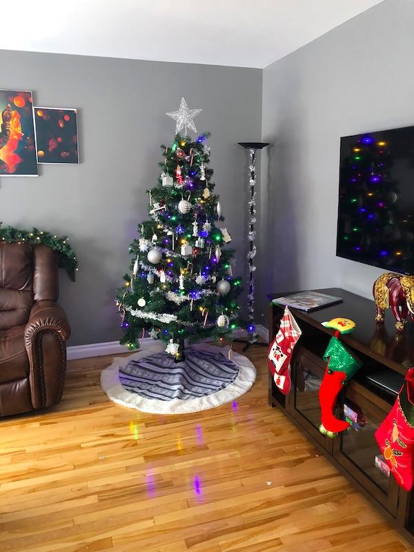 a Christmas tree and stockings hung on a mantel