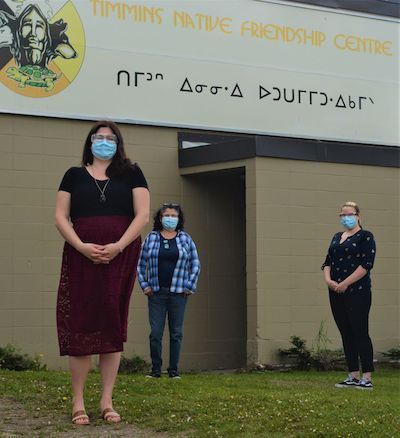 two masked woman and one masked man stand in front of a friendship centre