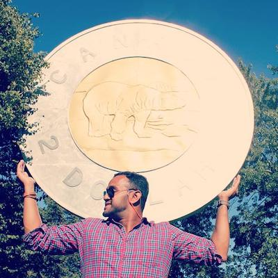 man with arms raised in front of a giant coin replica