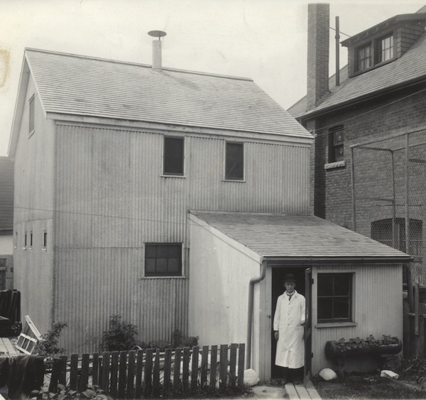 man in a wood coat standing in front of a wooden building