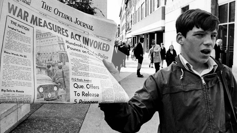 """Boy holds newspaper saying """"War Measures Act Invoked"""""""