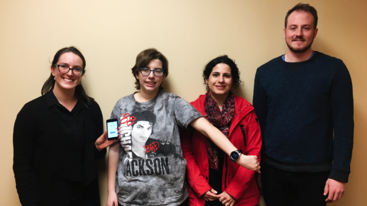 Three women and a man pose. The two women on the left are showing off a smartphone and a smart watch.