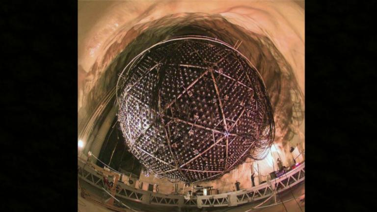 Large sphere suspended from a ceiling made of rock.