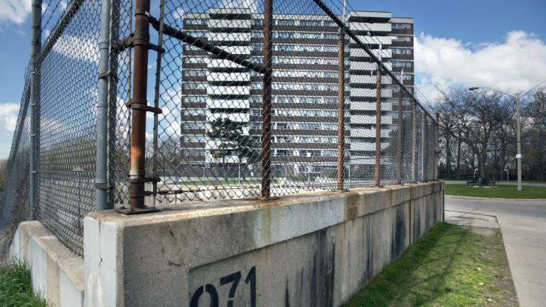 Fenced area in the foreground, apartment in the background