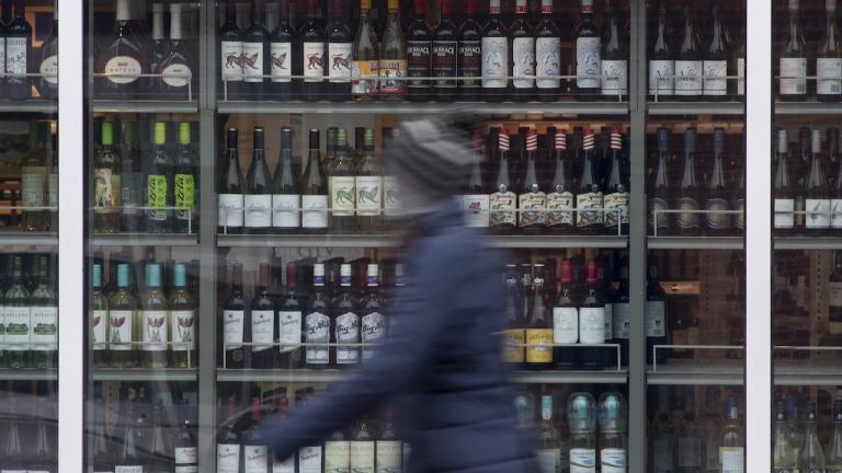 out-of-focus person walks past rows of wine bottles from the article Is Ontario finally ready to be logical about alcohol?