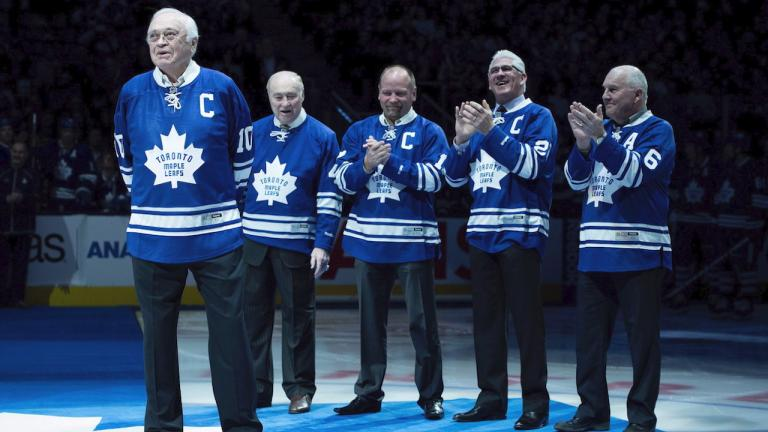 a row of older men stand on a rink wearing hockey jerseys from the article  'That pride of being a northerner': Remembering Leafs great George Armstrong