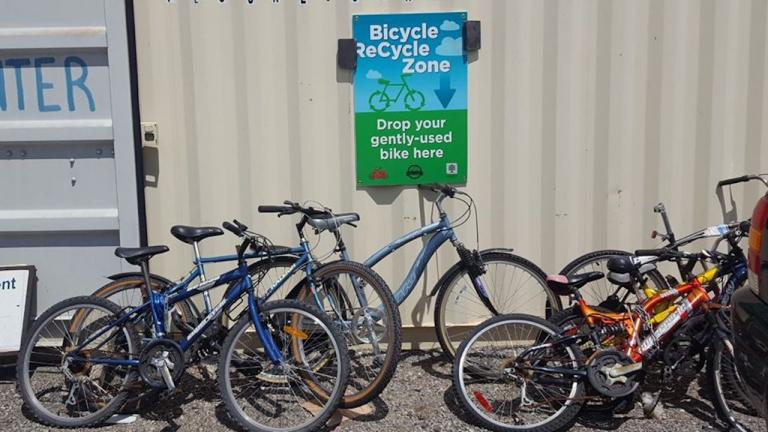 "a number of bikes sit near a sign for the ""bicycle recycle zone"""