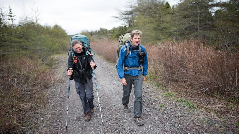 A man and a woman hike up a trail from the article Hiking Canada's Great Trail in the name of citizen science