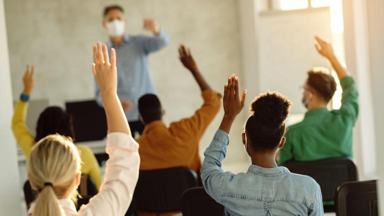 students with hands raised in front of a masked instructor