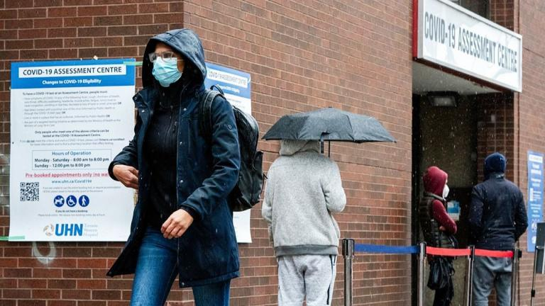 Person with mask walks away from COVID-19 assessment centre
