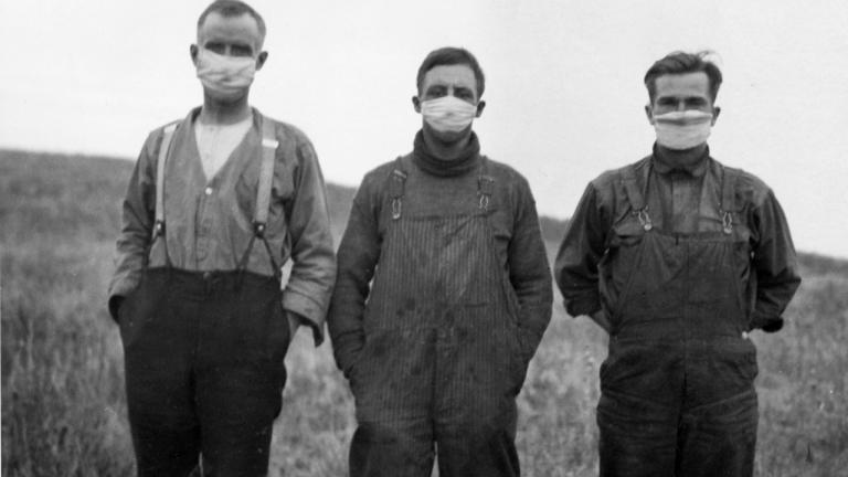 archival photo of three men wearing masks during Spanish Flu pandemic