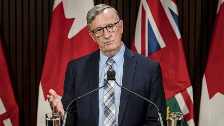 man standing behind a podium in front of flags from the article Ontario has drawn its COVID-19 red line. What now?