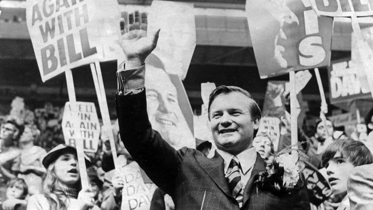 black and white photo of man in suit waving in midst of crowd with signs