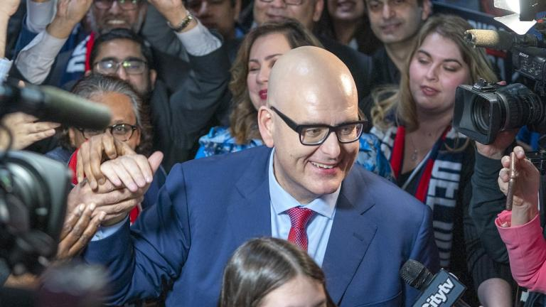 a bald man in glasses and a suit surrounded by people