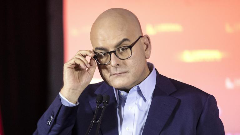 bald man in suit with one hand holding the side of his glasses