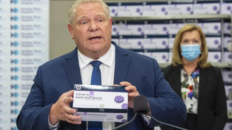 a man holds up a COVID-19 testing kit while a masked woman stands in the background from the article How Ontario's new rapid COVID-19 tests will — and won't — change the game