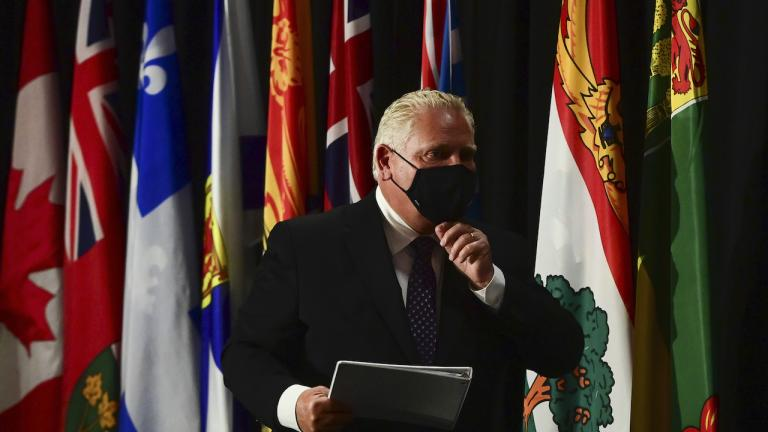 A man adjusts his masks in front of a row of flags from the article Best-case scenario for the government: Learn from its COVID-19 failures