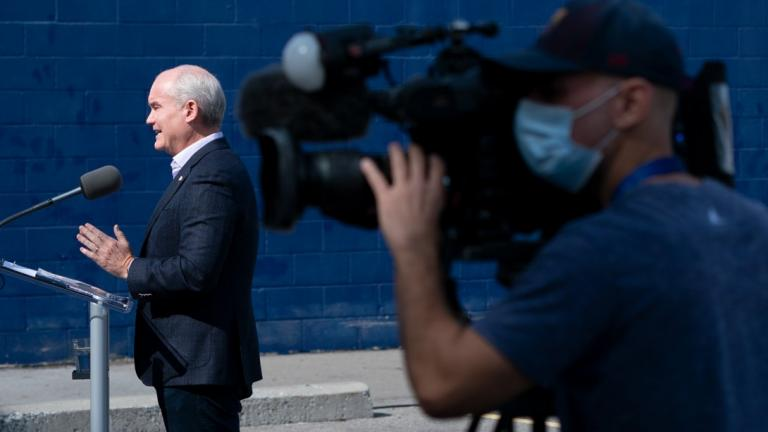 Man in background talks into microphone while man with video camera shoots in the foreground
