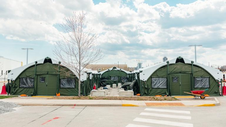 two large army-green tents in a parking lot from the article How do you build a field hospital?