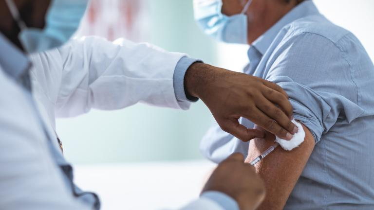 closeup of doctor give a man a vaccination in his arm