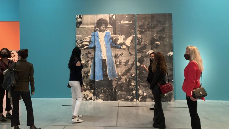 people stand in front of a painting of a girl in a blue coat, on a blue wall from the article 'For us, by us': How a new Caribbean exhibition is changing the AGO