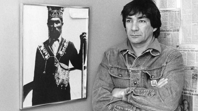 a man stands next to a portrait from the article 'A great land defender and defender of the people': Remembering Chief Gary Potts