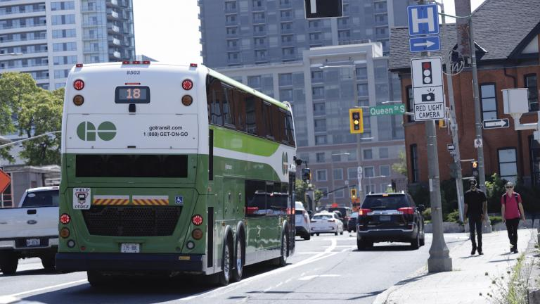 a green bus on a busy city street; two pedestrians on the sidewalk from the article What mobility data can — and can't — tell us about COVID-19