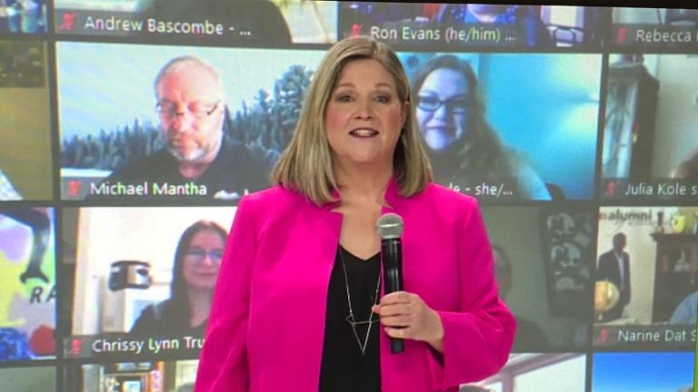 a woman in a pink jacket holding a microphone in front of a wall of video chats