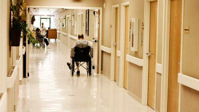 Man in wheelchair goes down hospital hallway.