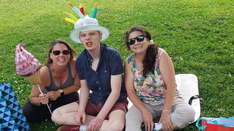 two women and young man wearing a birthday hat