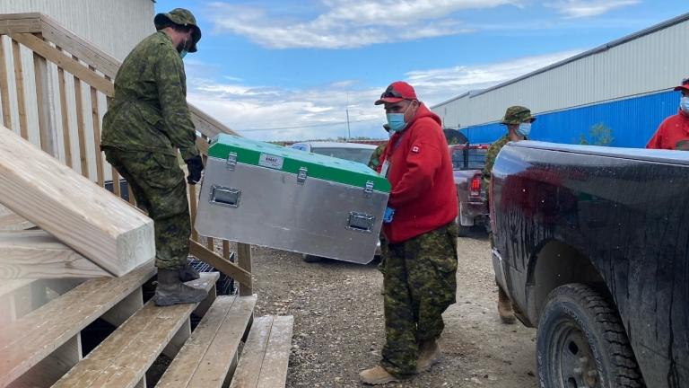 two men carry a box of supplies from the article Kashechewan's COVID-19 emergency had pre-pandemic roots