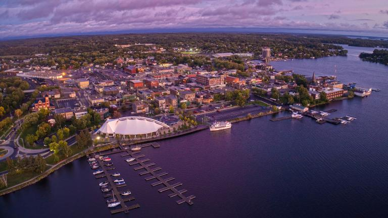 overhead shot of a city on a lake at dusk from the article COVID-19 fears are fanning the flames of racism in Kenora