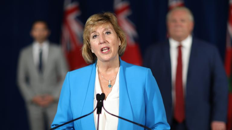 woman in a blue jacket stands behind a microphone