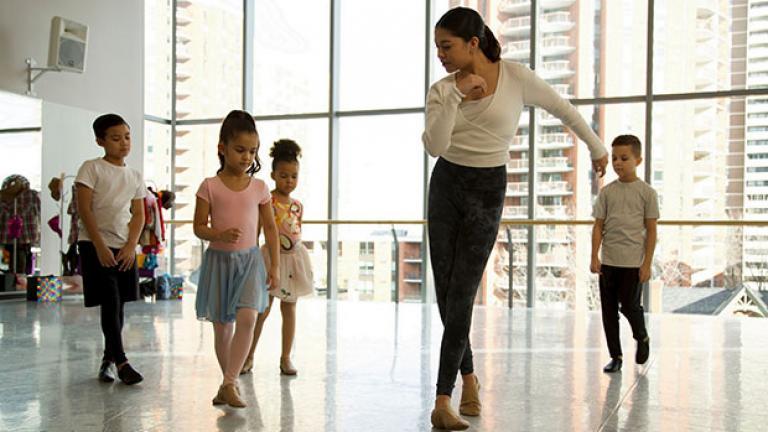 Teacher shows children a dance move