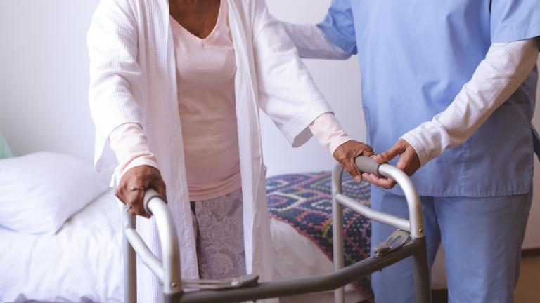 An LTC worker assists an elderly resident