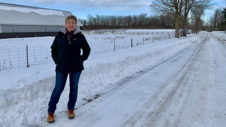 a woman stands on a snowy road in front of a fence