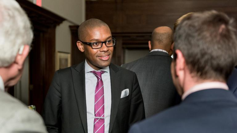 a man in a suit and glasses talks to two other men