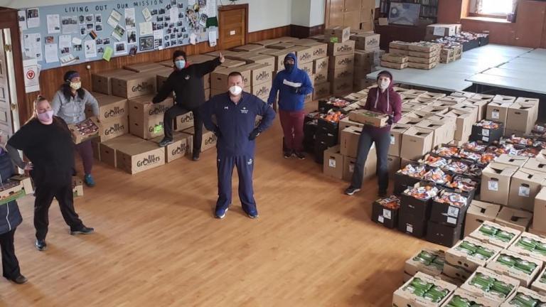 Workers stand in front of crates of food from the article Ezhi-noojimodiziyang ezhichigeyang ji-debinigosiwang aakoziwin
