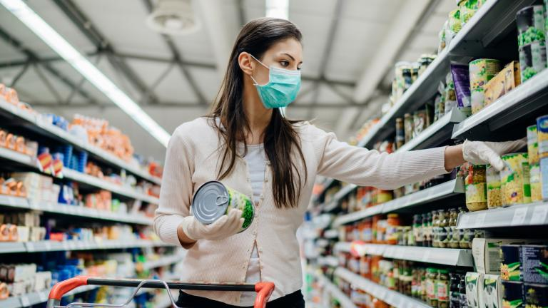 woman in mask shopping for groceries from the article Who can — and should — make masks mandatory in Ontario