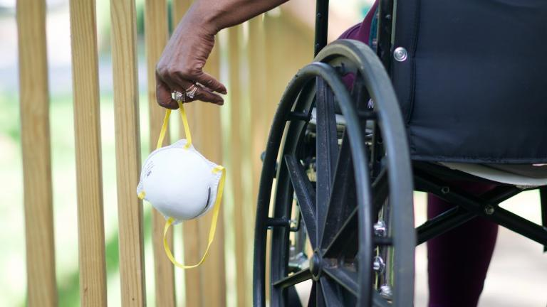 person in a wheelchair holding a mask