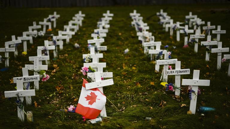 rows of white crosses with a Canadian flag in the foreground from the article 'These are all people': How to appreciate the individual lives behind the COVID-19 numbers