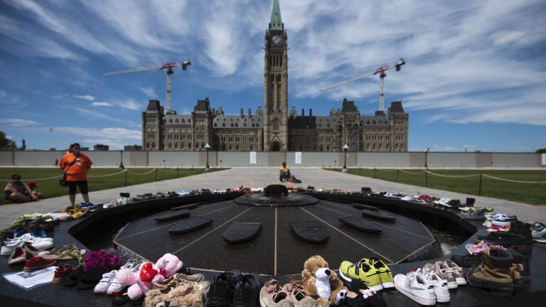 shoes arrange in a circle in front of Parliament Hill from the article Residential schools are not a footnote in Canada's history. They are its past and present