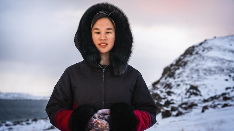 Mumilaaq Qaqqaq, MP for Nunavut, stands againts a snowy background. Her hands are clasped in front of her, and she's wearing mittens